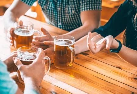 Photo for Happy Friends Drinking Beer And Clinking Glasses At Pub, Leisure, Friendship And Celebration Concept. Group Of Young People While Relaxing At Bar - Royalty Free Image