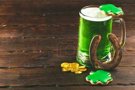 Fond de jour Patrick avec un verre de bière verte et de pain d'épice de trèfle avec pièces d'or sur fond en bois