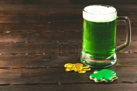 Patrick's day background with a Glass of green beer and clover gingerbread with gold coins on wooden background