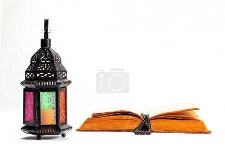 Islamic Holy Book Quran with rosary beads under soft light on White Background with a shining lantern Fanus. Ramadan concept.Three months.