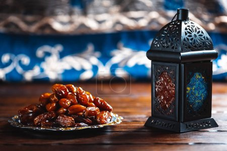 The Muslim feast of the holy month of Ramadan Kareem. Beautiful background with a shining lantern Fanus and dried dates on wooden boards. Free space for your text
