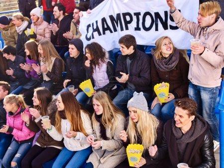 Sport fans holding champion banner on tribunes. Winter weather.