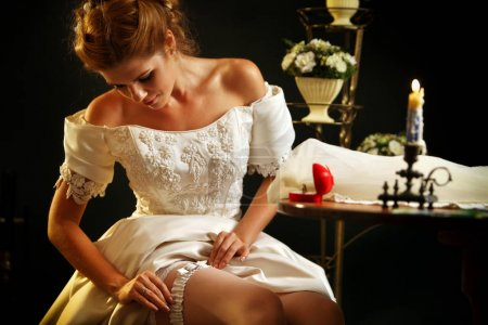 Wedding night preparing garter. Bride undressing.