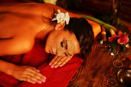 Photo for Massage of woman in spa salon. Girl on candles background in massage spa salon. Luxary interior in oriental therapy salon. Top view of female have relax after sports training. - Royalty Free Image