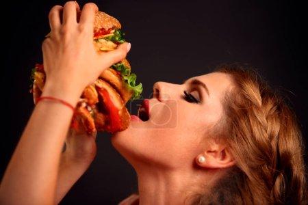 Woman eating hamburger. Student consume fast food.