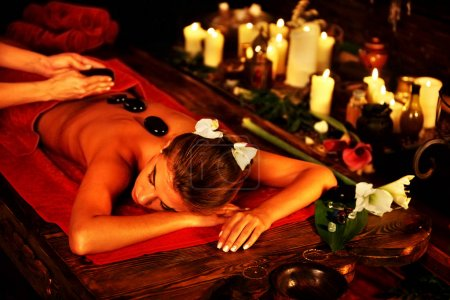 Massage stones of woman in spa salon. Girl candles background.