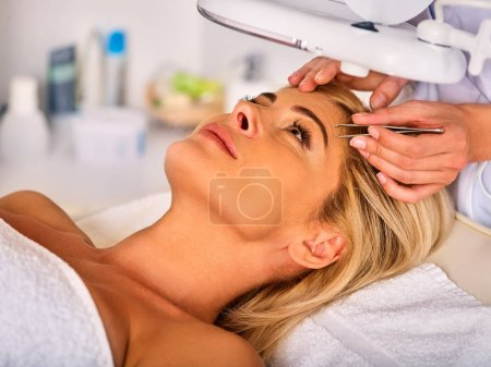 Eyebrow treatment of woman middle-aged in spa salon.