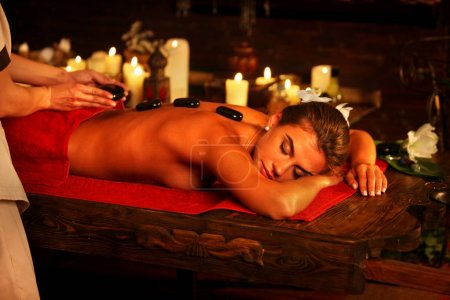 Massage basalt hot stones of woman in spa salon. Girl candles background.