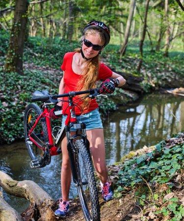 Photo pour Bicyclette adolescent avec dames vélos dans le parc d'été. Femmes vélo de route pour courir sur la nature. Adolescente en casque cyclisme traversant l'eau. Voyage à vélo est bon pour la santé en plein air . - image libre de droit