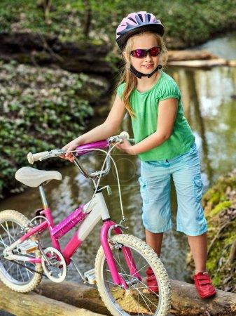 Photo pour Vélos enfants avec dames vélos dans le parc d'été. Enfant vélo de route pour courir sur la nature. Enfant fille en casque cyclisme traversant l'eau. Voyage à vélo est bon pour la santé en plein air . - image libre de droit