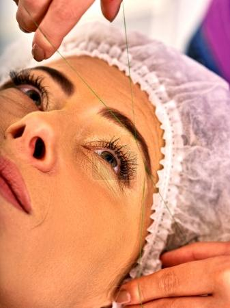 Eyebrow threading of woman middle-aged in spa salon.