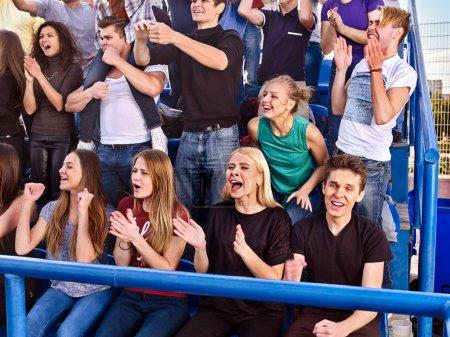 Photo pour Les fans applaudissent dans le stade. Les gens du groupe attendent votre équipe préférée et s'inquiètent des tribunes. Les jeunes soutiennent votre équipe préférée. Les jeunes hommes et les jeunes femmes sont habillés de vêtements légers et de jeans . - image libre de droit