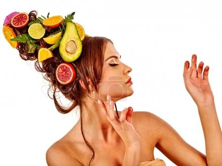 Hair mask from fresh fruits on woman head and spring flowers.