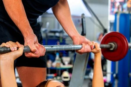 Photo for Fitness friends workout gym. Woman working on bench press. Cropped shot of she lifting barbell. Trainer backs girl while taking exercises. - Royalty Free Image