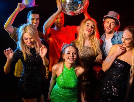 Photo pour Dansante avec le groupe de personnes dansant. Les femmes et les hommes sont amuser en boite de nuit. Heureuse jeune fille en robe de soirée verte sur le premier plan et disco ball sur fond. - image libre de droit