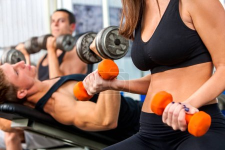 Woman holding dumbbell workout at gym.