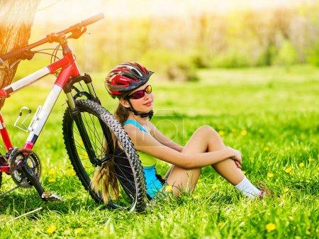Photo pour Fille voyageant à vélo dans le parc d'été. Le cycliste se repose près du vélo. Le vélo est bon pour la santé en été et au printemps . - image libre de droit