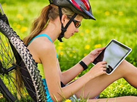 Photo for Woman traveling bicycle in summer park. Bicyclist girl watch on tablet computer. Girl counts pulse after sport training and is looking for way to navigator. Cycling is good for health and travelling . - Royalty Free Image