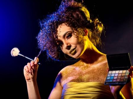 Woman with decorative cosmetics. Girl holds eye shadow and brush.