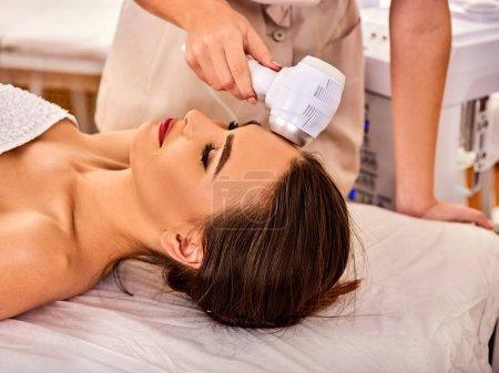 Photo pour Traitement facial par ultrasons sur machine à ultrasons. Femme recevant un massage par ascenseur électrique au salon de spa. stimulation électronique muscles féminins thérapie par microcourant. Technologies de rajeunissement . - image libre de droit