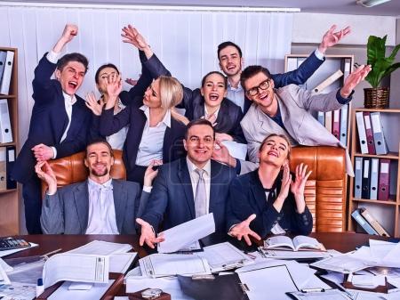 Photo pour Vie de bureau d'affaires personnes de personnes de l'équipe sont heureux avec coup de main assis à table. Armoires à dossiers en arrière-plan. Personnes en costumes heureux avec accord fructueux et célébrer le succès au bureau. - image libre de droit