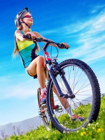 Photo pour Femme voyageant à vélo dans le parc d'été. Enfant vélo de route pour courir sur l'herbe verte. Faire du vélo est bon pour la santé. Heureux cycliste à l'avenir . - image libre de droit
