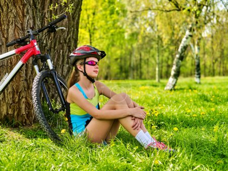 Photo for Woman traveling bicycle in summer park. Bicyclist girl watch on smart watch. Girl counts pulse after sport training. Girl hugs herself by knees is dreaming, looking at sky. - Royalty Free Image