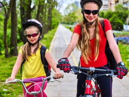 Bicycle path with children. Girls wearing helmet with rucksack .