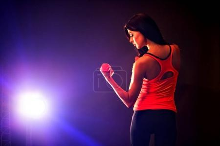 Photo for Fitness girl exercising in gym with dumbbells. Woman has slim stomach works in multi-colored rays of sport room. Portrait of full-length in profile. Back view of beautiful back. - Royalty Free Image