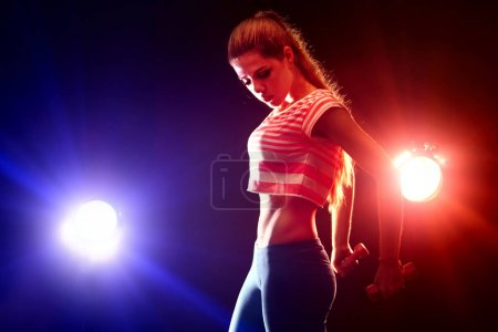 Photo for Fitness girl exercising in gym with dumbbells. Woman has slim stomach works in multi-colored rays of sport room. Portrait of full-length in profile. Flat stomach as motivation for sports - Royalty Free Image