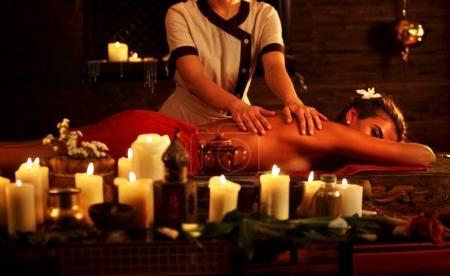Photo pour Massage de la femme dans le salon spa. Fille sur fond de bougies traite le problème de retour. Luxary intérieur avec travail masseuse. Fond de Pot de Shirodhara. Récolte de dos nu a se détendre. Médecine alternative. - image libre de droit