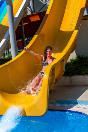 Swimming pool slides for woman on water slide at aquapark.