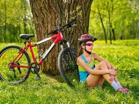 Photo for Girl traveling bicycle in summer park. Bicyclist has rest near bike. Cycling is good for health in summer and spring. Girl is waiting for guy on date. - Royalty Free Image
