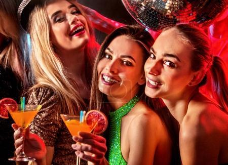Photo pour Club de nuit disco femme. Dansante avec le groupe de personnes dansant. Amusant et boire martini cocktail en boite de nuit. Fille heureuse sur le premier plan et disco ball sur fond. Parti après avoir travaillé dans le club. - image libre de droit