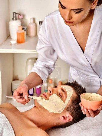 Photo pour Masque facial de boue de l'homme dans le salon spa. Massage avec visage plein d'argile. Fille sur avec la salle de thérapie. Homme allongé sur le lit de la spa. Esthéticienne avec bol procédure thérapeutique. Pommade contre l'acné. - image libre de droit