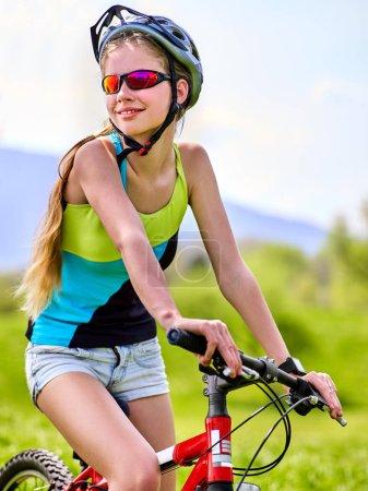 Photo pour Femme voyageant à vélo dans le parc d'été. Femmes vélo de route pour courir sur l'herbe verte ciel bleu aganiste avec des nuages blancs. Faire du vélo est bon pour la santé. Femme en voyage scolaire . - image libre de droit