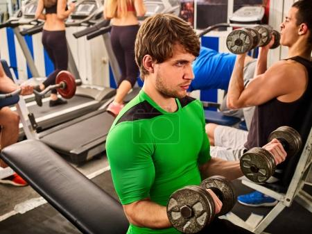 Friends in gym fitness workout equipment. Man do dumbbell exercise.