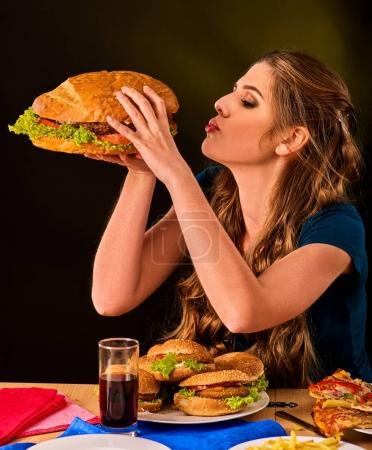 Woman eating french fries and hamburger with pizza.