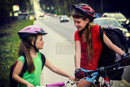 Bicyclist child ride on city bicycle path . Girls wearing helmet .