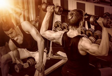 Men with barbell at gym. Color tone background.