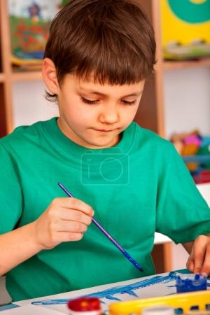 Photo for Small student boy painting in art school class. Child drawing by paints on table. Portrait boy in childrens club. Craft drawing education develops creative abilities of children. - Royalty Free Image