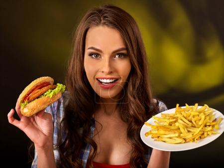 Woman eating french fries and hamburger on table.