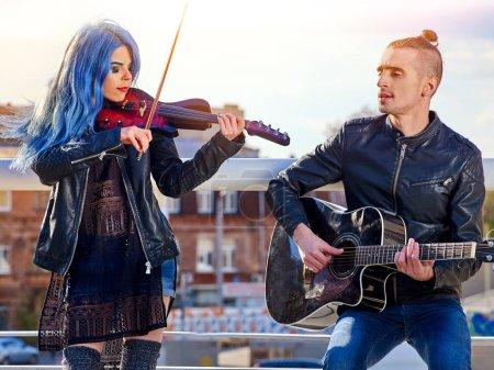 Photo pour Groupe de musique festival dans le parc de la ville. L'homme joue de la guitare et chante la chanson sur l'amour et la fille l'accompagne au violon. - image libre de droit