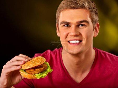 Man eating hamburger. Boy bite of very big burger