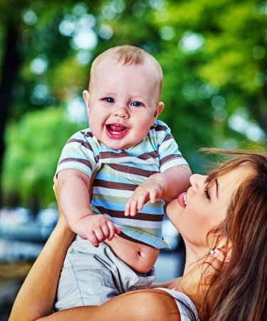 Photo for Baby in park outdoor. Kid on moms hands. Happy beautiful mom and child summer sunrise or sunset on city outside. Portrait of happy loving mother and her son spring outdoors. Adoption of child idea. - Royalty Free Image