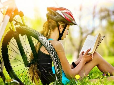 Photo pour Femme voyageant à vélo dans le parc d'été. Fille lire le livre sur le repos près de votre véhicule. Le vélo est bon pour la santé. Cycliste se prépare pour l'examen dans le parc. Fille s'amuse en vacances . - image libre de droit