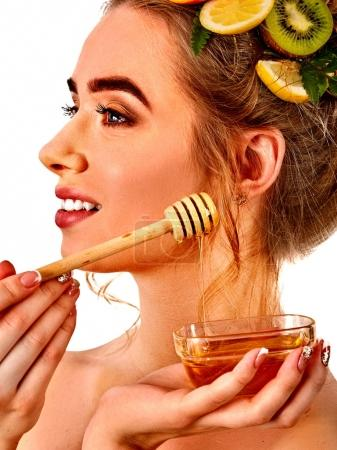 Honey facial mask with fresh fruits for hair and skin on woman head.