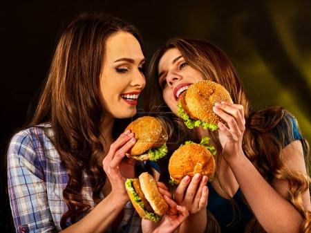 Photo for Hamburger fast food with ham and group people. Good Fast food concept. Friends two women eating sandwich junk in party. Girls eat up after diet. - Royalty Free Image