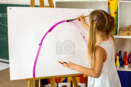 Children painting finger on easel. Group of kids with teacher.