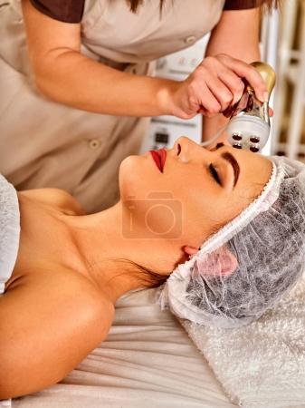 Woman massage beauty salon. Electric stimulation female skin care.